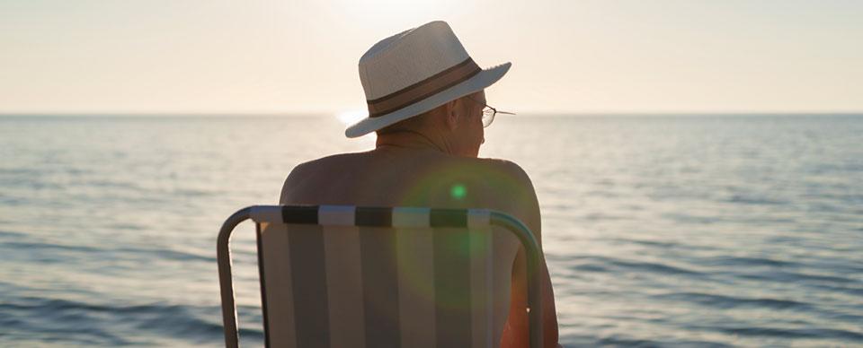 försäkring direkt sjuk försäkring, man i hatt sitter i en solstol vid havet i solnedgång